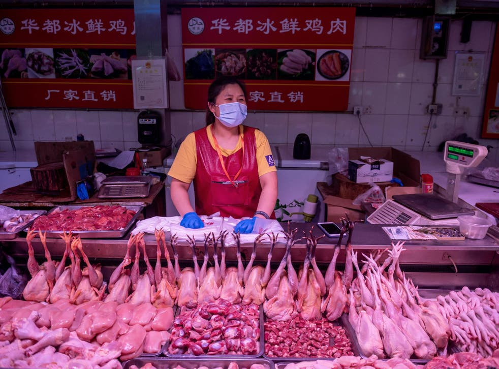 A vendor waits for customers at a chicken stall at a market in Beijing