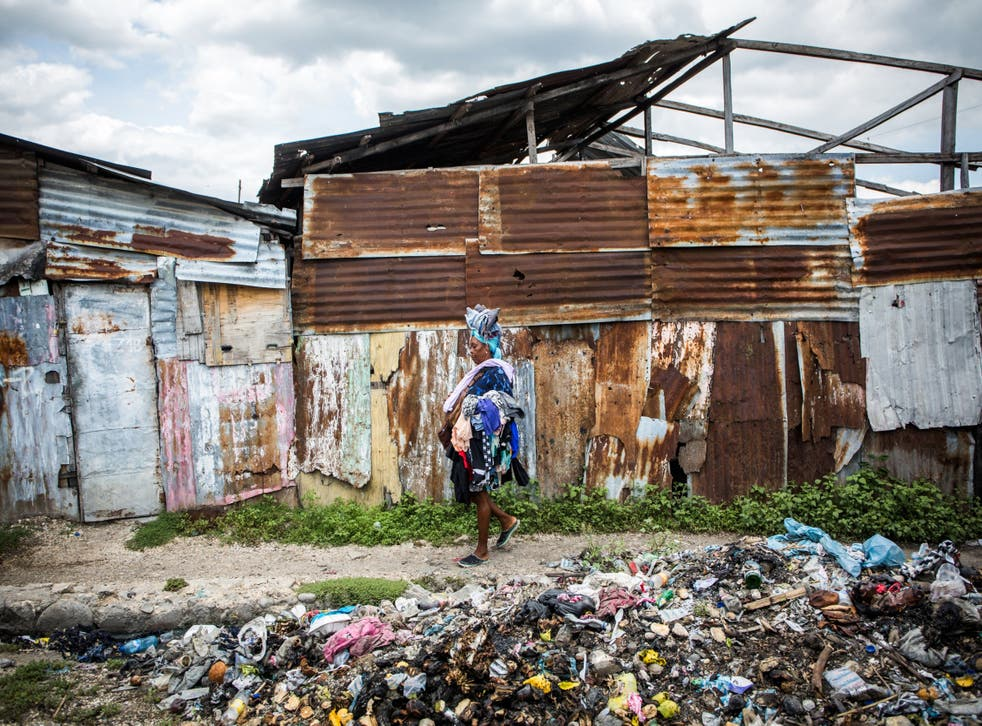 A woman scavenges for clothes in the rubbish mounds of La Saline slum in Port-au-Prince in July