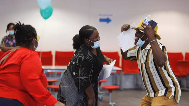 Parents and a student react after checking GCSE results at Ark Academy in London