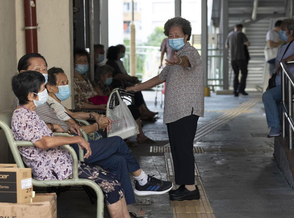 People wearing face masks as a precautionary measure against the Covid-19 coronavirus sit together in Hong Kong