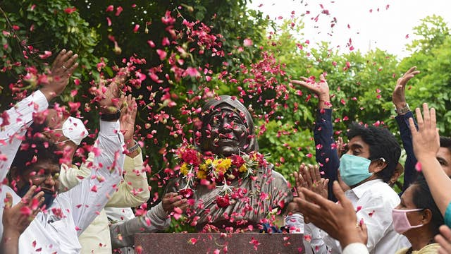 People scatter rose petals on a statue of Mother Teresa marking her 110th birth anniversary in Ahmedabad