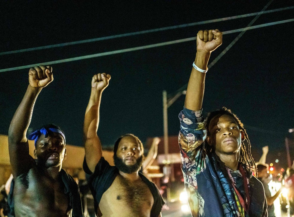 Protesters raise their fists during a demonstration against the shooting of Jacob Blake in Kenosha, Wisconsin