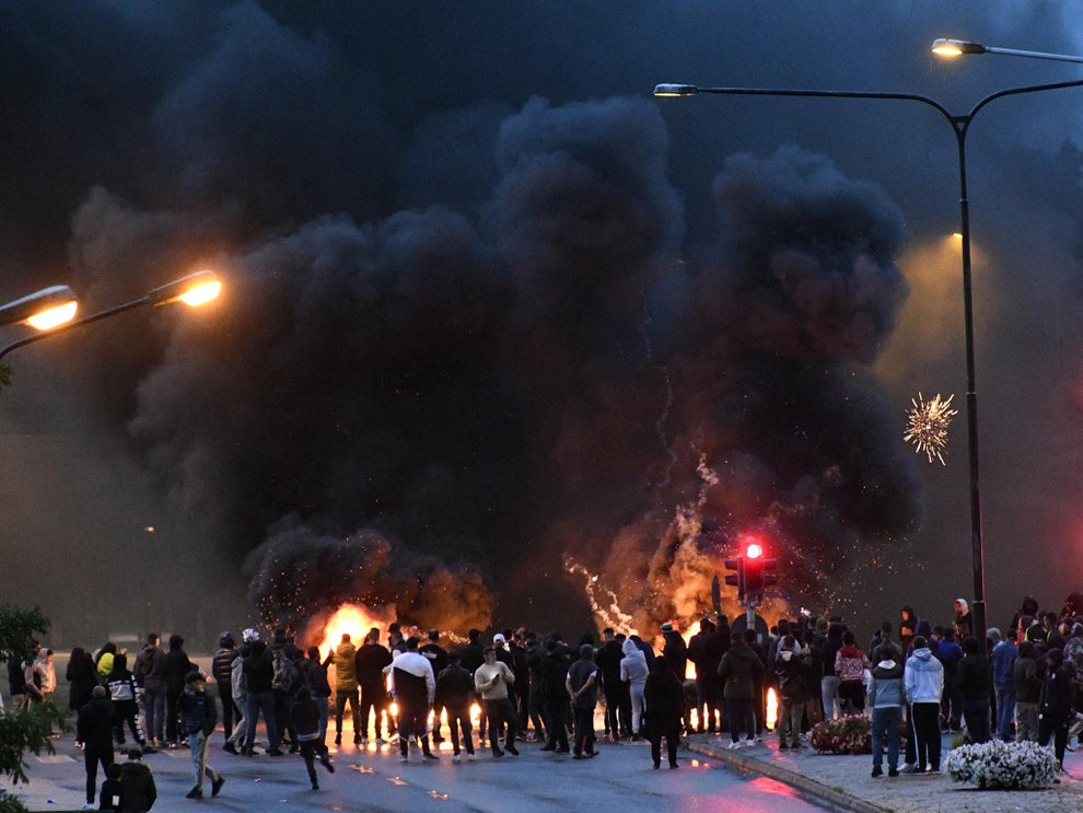 Smoke billows from burning tyres, pallets and fireworks  as hundreds protest the burning of the Quran in Malmo