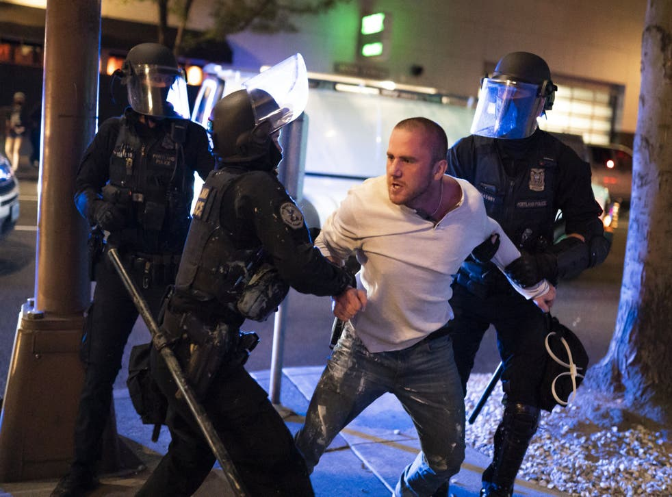 Portland police hold back a man who was with the victim of a fatal shooting as he reacts in minutes after the incident on August 29, 2020 in Portland, Oregon