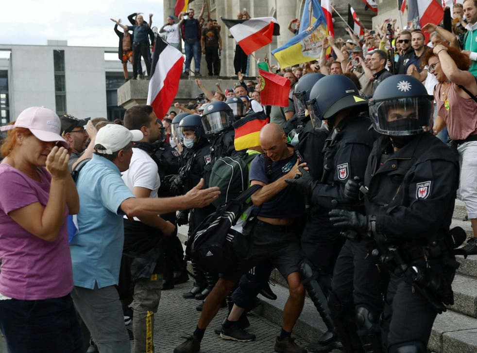Police scuffle with protesters in front of the Reichstag building in Berlin, Germany.