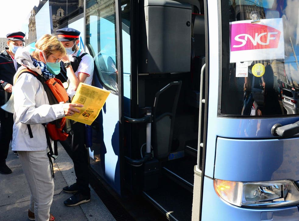 SNCF passengers board a bus in front of Bordeaux St-Jean train station in Bordeaux, southern France to reach stations further south after thousands of travellers were stranded aboard their train in the region following electrical incidents