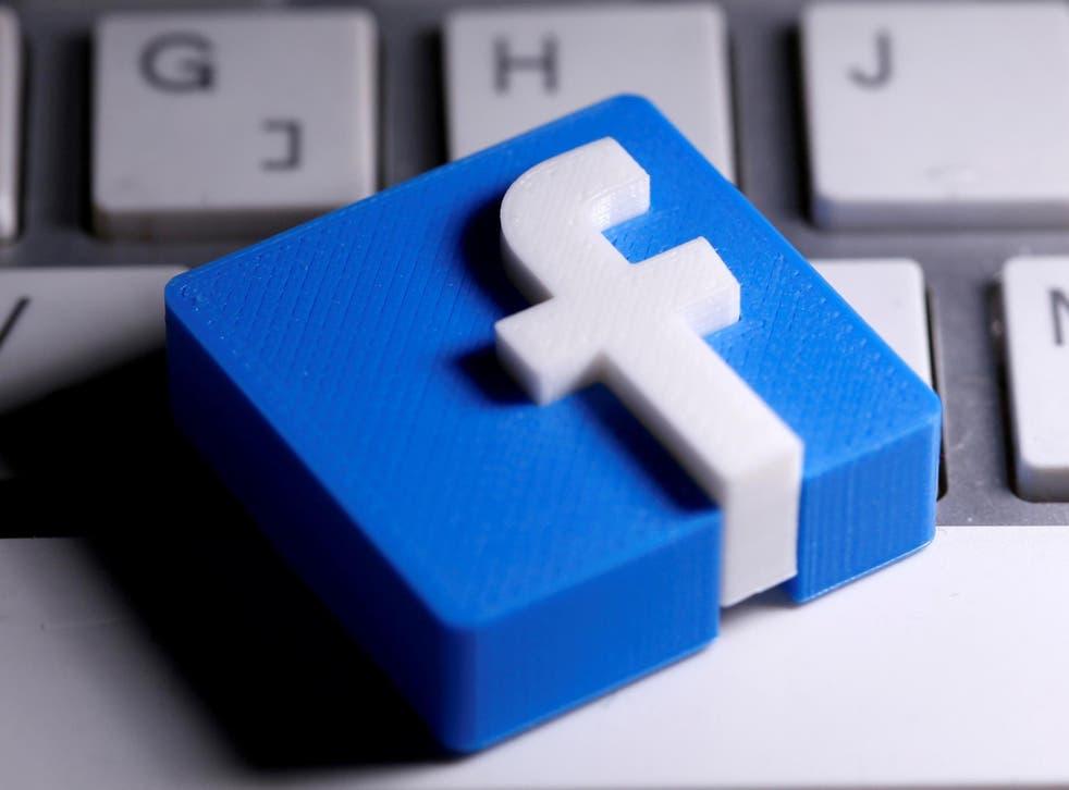 Se ve un logotipo de Facebook impreso en 3D colocado en un teclado en esta ilustración