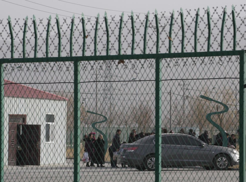 """People line up at a """"re-education"""" centre in Xinjiang province, China, in December 2018."""