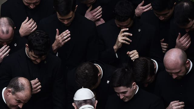 Pope Francis prays with priests at the end of a limited public audience at the San Damaso courtyard in The Vatican