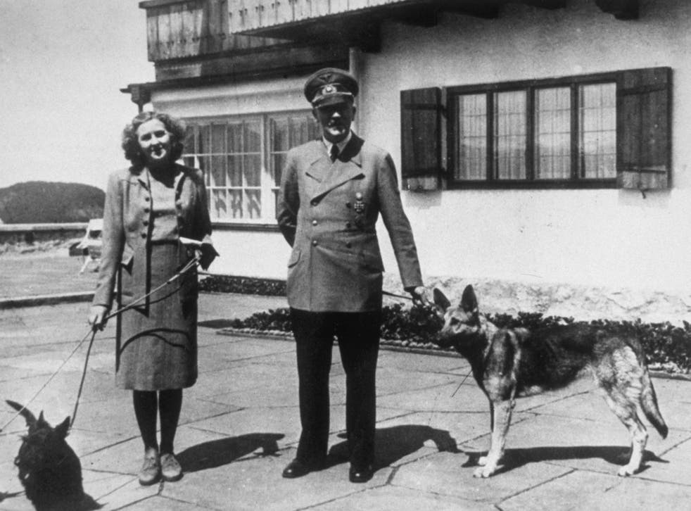 <p>Hitler with Eva Braun, his supposed wife, photographed with their dogs at Berchtesgaden</p>